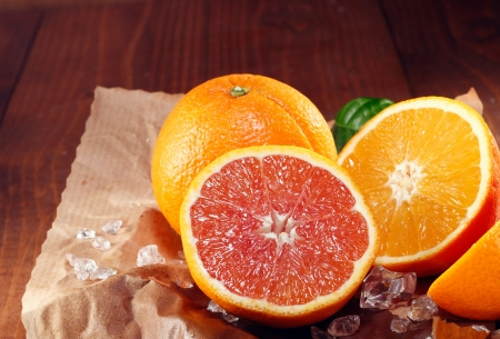 colouration: Halved fresh orange varieties with the traditional orange coloured pulp and the cara cara orange with its red-pink colouration on crumpled grungy brown paper