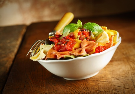 tilted view: Delicious colourful Italian bow tie pasta served with tomato and basil in a white ceramic dish with a fork on an old wooden table, tilted view