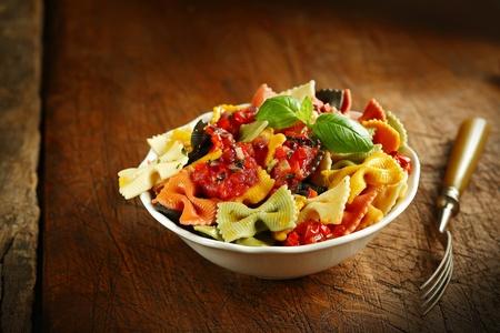 tie bow: Multicolore italiana farfallino pasta condita con pomodoro e guarnito con basilico servito in una ciotola di ceramica bianca con una forchetta su un vecchio tavolo di legno Archivio Fotografico