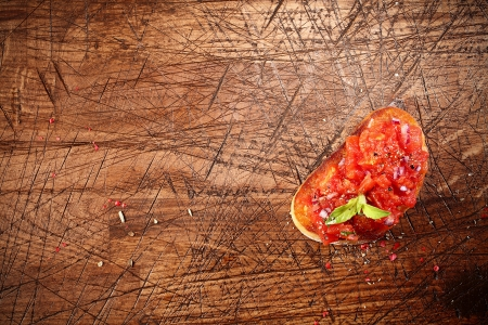 scored: Overhead view of colourful red tomato bruschetta on toasted or grilled baguette lying on an old grunge badly scored wooden chopping board with copyspace