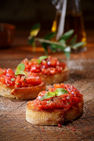 scored: Colourful red tomato bruschetta on slices of crisp crusty toasted or grilled baguette lying on an old grunge badly scored wooden chopping board, low angle view with copyspace Stock Photo