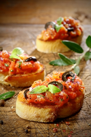 crusty: Tomato bruschetta topped with olive and basil on slices of crisp crusty toasted or grilled baguette lying on an old grunge badly scored wooden chopping board, low angle view with shallow dof