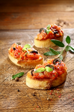 Preparing vegetable bruschetta with finely chopped tomato, onion and seasonings served on slices of crisp golden crusty toasted baguette on a grungy old wooden surface with copyspace photo