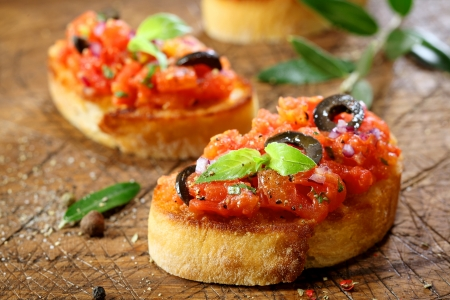 crusty: Preparing delicious Italian tomato bruschetta with chopped vegetables, herbs and oil on grilled or toasted crusty baguette sprinkled with seasoning and spices on an old grungy wooden chopping board Stock Photo