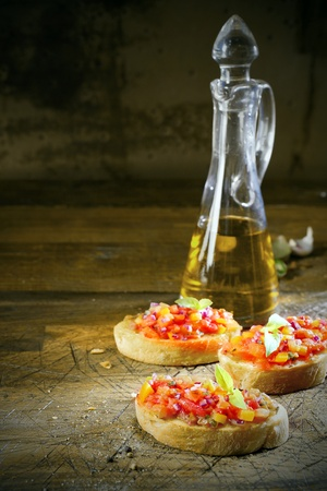 Preparing bruschetta in a country kitchen with three slices of toasted sliced baguette topped with chopped vegetables and oil with a decanter of virgin olive oil behind Stock Photo - 19119323