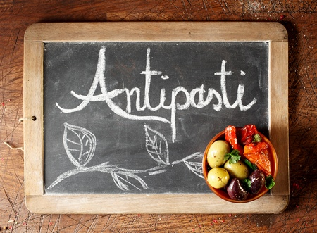 antipasti: Chalkboard Antipasti sign with handwritten text and decorative foliage with a small bowl of black and green olives and hot chilli peppers in the corner, overhead view on a wooden background