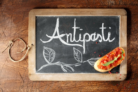 antipasti: Overhead view of colourful red tomato bruschetta on an Antispasti sign handwritten on a small framed blackboard lying on a wooden background Stock Photo