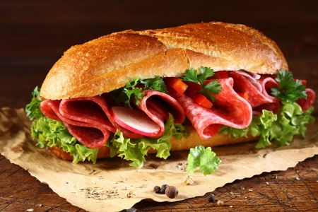 thinly: Freshly baked golden crusty baguette filled with fresh lettuce and thinly sliced salami seasoned with spices on crumpled brown paper Stock Photo