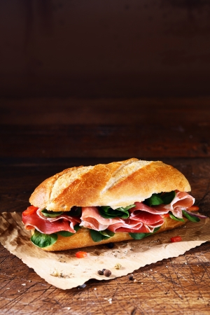 Fresh basil and thinly sliced cold ham on a crusty freshly baked baguette on a sheet of crumpled paper photo