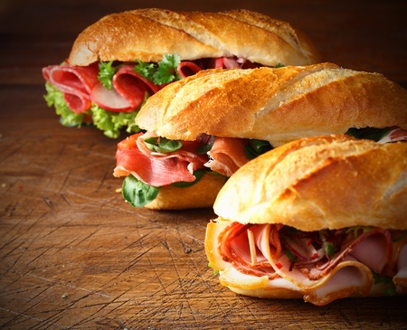 crust crusty: Assorted delicious baguette sandwiches filled with thinly sliced ham or salami and fresh green lettuce or basil arranged in an oblique row on an old wooden table with copyspace