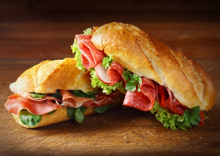 sandwich: Delicious salami and ham baguettes with fresh lettuce and basil on an old wooden kitchen table top