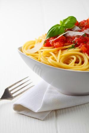 comida italiana: Cierre de tiro de un recipiente blanco de pasta con salsa de tomate y albahaca fresca con una servilleta blanca y tenedor. Foto de archivo