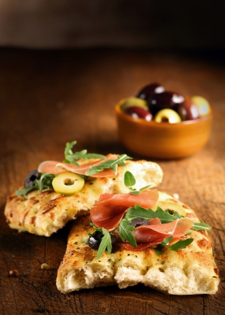 ovenbaked: Serving of fresh traditional oven-baked Italian focaccia bread with ham, olives and rocket on a wooden table top with copyspace Stock Photo
