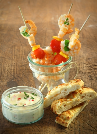 Tasty appetizers of seafood cocktail sticks with shrimps, cheese and tomato standing in a jar alongside fresh focaccia bread and a tub of tartare sauce photo