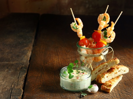ovenbaked: Delicious prawn or shrimp appetizers with cherry tomatoes served with tartare sauce and fresh oven-baked Italian focaccia bread on an old wooden table with copyspace