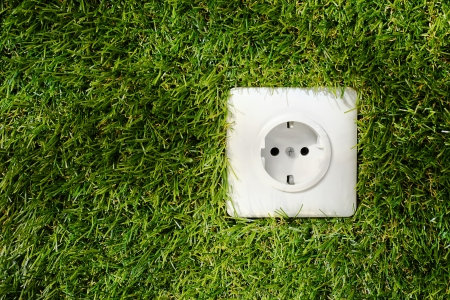 Overhead view of a white plastic outdoor electrical power socket embedded in green grass with copyspace alongside Stock Photo - 19119422