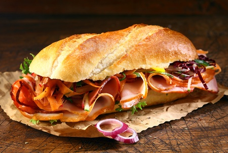 Delicious crusty baguette sandwich with ham, lettuce and onion on a small grungy crumpled sheet of brown paper on a wooden table