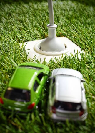 Outdoor electrical power socket in green grass with a plug and cable inserted and two toy model cars in the foreground Stock Photo - 19271374