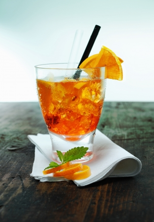 spritz: Serving of aperol spritz cocktail with ice garnished with mint leaves and orange rind on a folded napkin on an old wooden counter in a bar or club