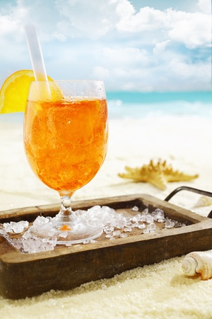 Delicious iced aperol spritzserved on a small wooden tray scattered with ice cubes on a hot tropical beach in summer sunshine photo