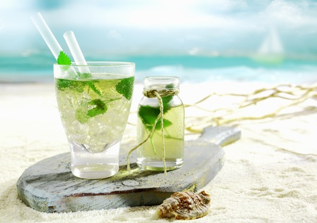 nettle: Refreshing cold Mojito cocktail with fresh mint served on an old wooden board lying on the golden sand of a tropical beach Stock Photo