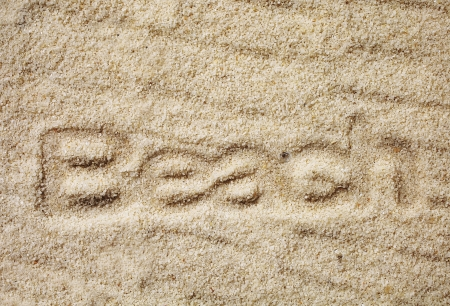 indentation: Golden sand with the indented word - Beach - on a tropical seashore with a ripple pattern caused by wind and water Stock Photo
