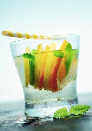 chilled: Glass of refreshing iced vodka or gin with slices of tangy citrus and fresh leaves of mint served on an old wooden countertop with a straw