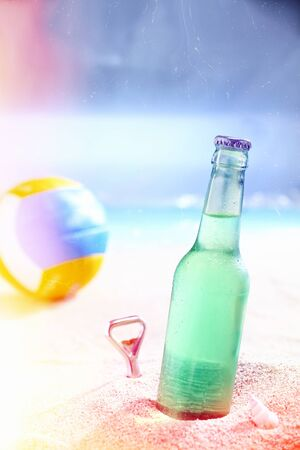unlabelled: Refreshing iced green soda in a capped unlabelled bottle standing in the golden sand of a hot beach in the tropics with an ocean background Stock Photo