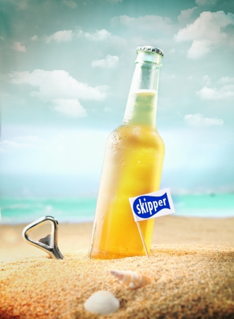 Capped bottle of chilled fruity orange soda or ale (beer) standing in the golden sand on a tropical beach with a bottle opener and Skipper sign. Look at my portfolio for more cocktails. photo