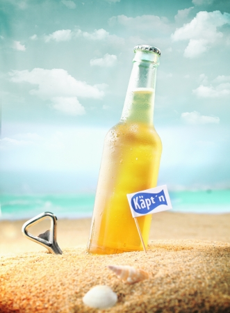 Beautiful photo of a chilled beer and a bottle opener on the beach tagged as Kaptn. photo