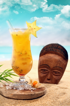 Colourful orange ca ram bola cocktail in a tall elegant glass served on a wooden tray scattered with crushed ice alongside a wooden mask standing upright in the beach sand on a tropical seashore photo
