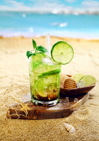 pics: Caipirinha Rum and lime cocktail garnished with mint leaves and served on a wooden board on the golden sand of a tropical beach