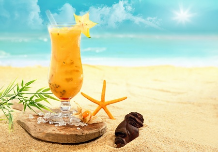 white  beach: Colourful carambola and orange cocktail ina tall glass served on a wooden board on a golden beach at a tropical holiday resort during an enjoyable summer vacation Stock Photo