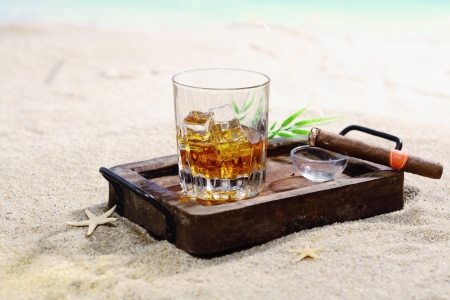 Beautiful image of drink on the rocks in a classy wooden tray on a sandy beach