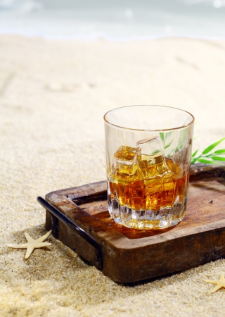 Beautiful photograph of a glass of drink with ice cubes in a classy wooden tray on the beach  Look at my portfolio for whole series of cocktails