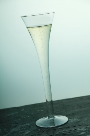 fluted: champagne, sparkling wine flute in a stylish tall fluted glass served on an old wooden bar counter, tilted angle