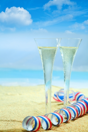 champagne flutes in elegant fluted glasses and a colourful red, white and blue twirled party streamer standing on the golden sand of a tropical beach with an azure blue ocean on a summer vacation. Look at my portfolio for whole series of cocktails. photo