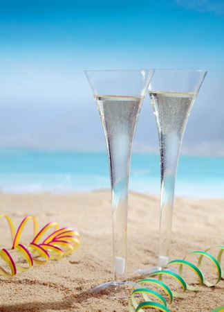 Beautiful photo composition of glasses of champagne on the beach. photo