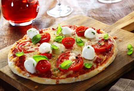 Delicious homemade freshly baked Italian pizza with a crisp golden crust garnished with fresh basil leaves served whole on an old wooden board photo