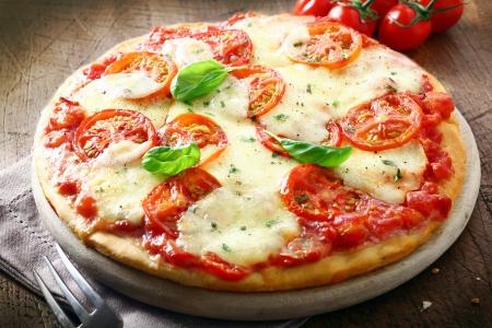 pizza: Italiaanse pizza met tomaat overgoten met gesmolten gouden kaas, kruiden en basilicum geserveerd op een ronde houten plank op een oude houten tafel