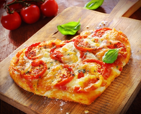 Heart shaped vegetarian pizza topped with cheese and tomato on an old wooden board signifying love of pizza, or romantic love for Valentines day or an anniversary photo