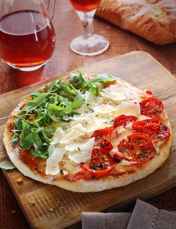 Italian pizza in the red, white and green colours of the national flag formed by the three toppings of tomatoes, cheese shavings and fresh rocket leaves on a wooden board served with a light red wine photo