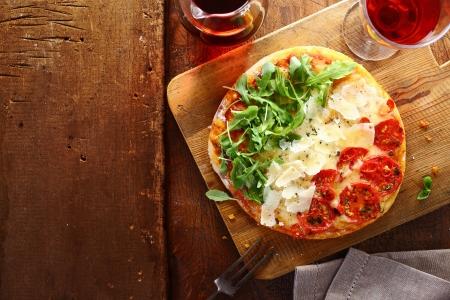 pizza: Patriottische Italiaanse tricolore pizza met strepen van rood, wit en groen in de kleuren van de nationale vlag gevormd door tomaat, kaas en verse rucola bladeren gebruikt voor de topping op een houten tafel met copyspace