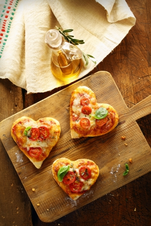 small plate: Cute heart shaped mini pizzas topped with cheese and tomato and garnished with fresh basil served on an old wooden board in the kitchen with virgin olive oil