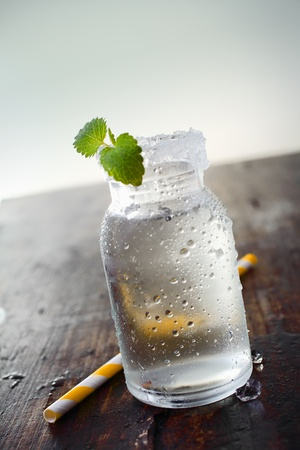 Image of a jar full of water with a small plant in it and a straw on the side. photo