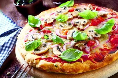 おいしいベジタリアン ピザ トマト、チーズ、マッシュルーム、玉ねぎをトッピングと新鮮なバジルの葉、木の板、高角度のビューを提供しています。多くのピザ私のポートで。 写真素材 - 19557168