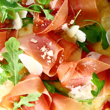 cured: Delicious thinly sliced Italian prosciutto ham and fresh rocket leaves served as a topping on a pizza base, closeup view