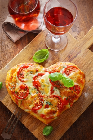 Overhead view of a tasty cheese and tomato vegetarian heart shaped pizza served on a wooden board with a glass of red wine