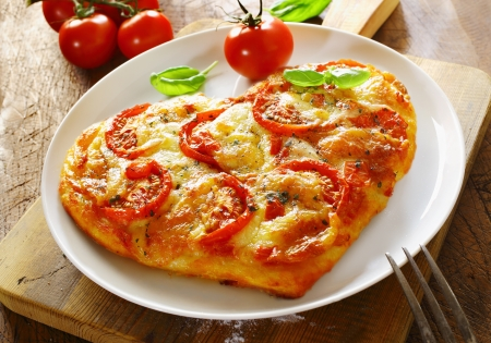 Delicious heart shaped Italian pizza with a topping of tomato and melted cheese served on a plain white plate with a fresh tomato and basil photo