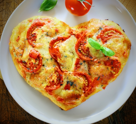 shape heart: Overhead view of a romantic heart shaped Italian pizza topped with a vegetarian topping of golden melted cheese and tomato on a plain white plate. More pizza at my port.